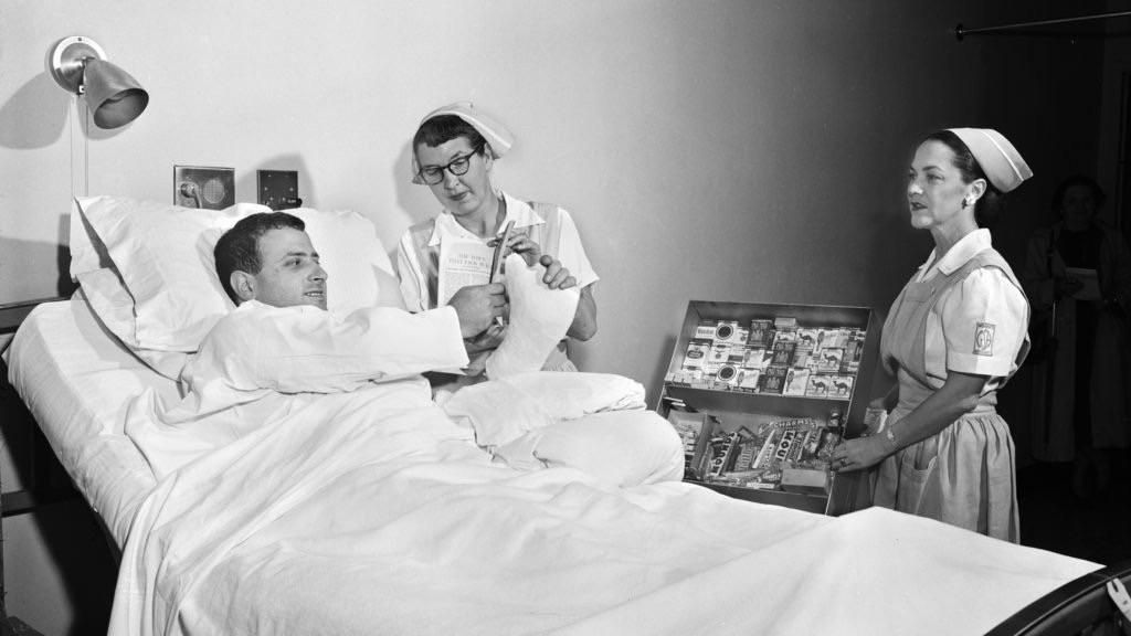 Man buying cigarettes from his hospital bed in the 1950s